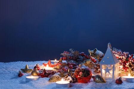 Christmas holiday card with decoration and glowing lantern in snow in the evening light
