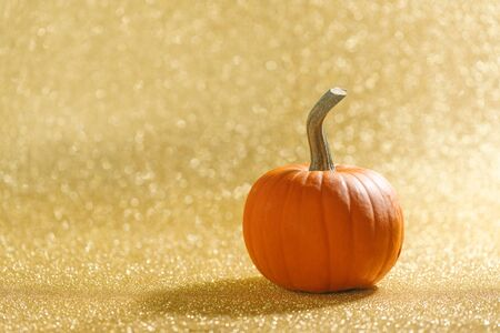 Pumpkin on golden glittery background with bokeh lights