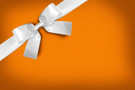 White gift bow on orange background with copy space Stock Photo