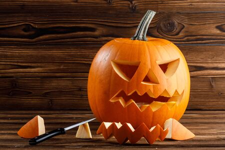 Carving of Halloween pumpkin in progress, pieces and cutting knife on wooden background Imagens