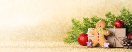 Christmas gift box gingerbread and decor on golden glitter background, copy space