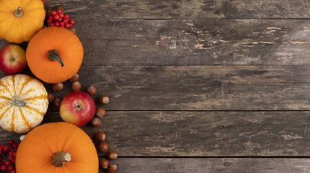 Autumn harvest still life with pumpkins, apples, hazelnuts on wooden background, top view Stock Photo