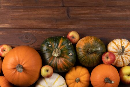 Autumn harvest still life with pumpkins and apples on wooden background, top view