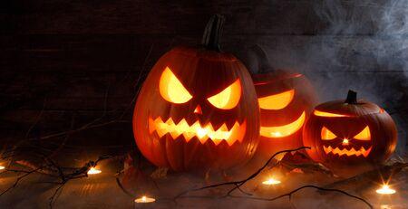 Cabezas de calabaza de Halloween jack o lantern y velas en la niebla sobre fondo de madera