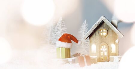 Christmas card with cozy small decorative house , gifts and Santa Claus cap on sleigh on snow over fairy tale winter fir forest background and falling snow . New Year design postcard . Copy space for text