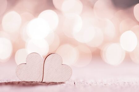Two wooden hearts on pink glowing bokeh hearts background for Valentines day Stock Photo