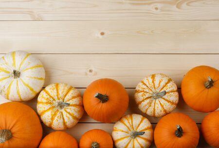 Viele orangefarbene Kürbisse auf hellem Holzhintergrund, Halloween-Konzept, Draufsicht mit Kopienraum