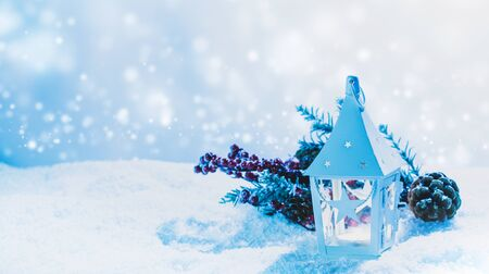 Burning candle in lantern and christmas decoration on snow