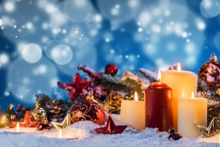 Christmas candles with traditional decorative stars , red baubles , pine cones and green branches on snow