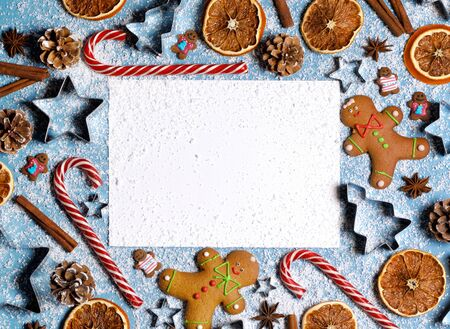 Christmas food frame. Gingerbread cookies, spices and decorations on blue background with copy space on blank card