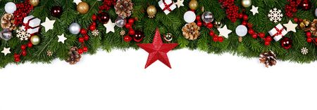 Christmas Border frame of tree branches on white background with copy space isolated, red and golden decor, berries, stars, cones Stock fotó