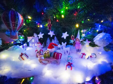 Beautiful glowing christmas tree with many present boxes and decor on snow