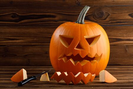 Carving of Halloween pumpkin in progress, pieces and cutting knife on wooden background