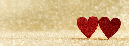 Two red wooden hearts on golden glowing bokeh hearts background for Valentines day Stockfoto