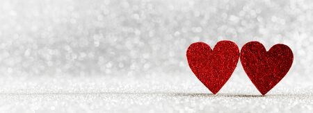 Two red wooden hearts on silver glowing bokeh hearts background for Valentines day