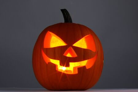 Glowing Halloween pumpkin head jack lantern on gray background Stockfoto