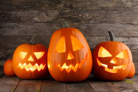 Three Halloween pumpkins head jack o lantern and candles on wooden table background Stockfoto