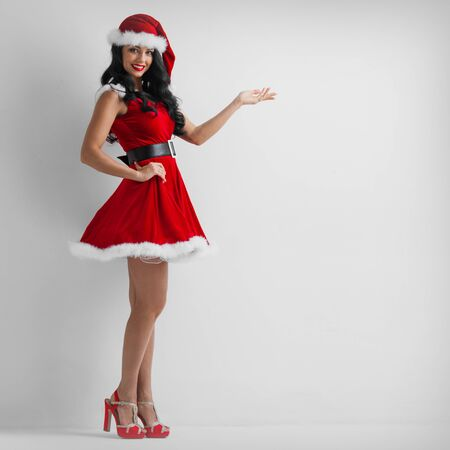 Christmas santa girl point hand, happy smile woman wear new year party Santa Clause costume show side empty copy space, white background