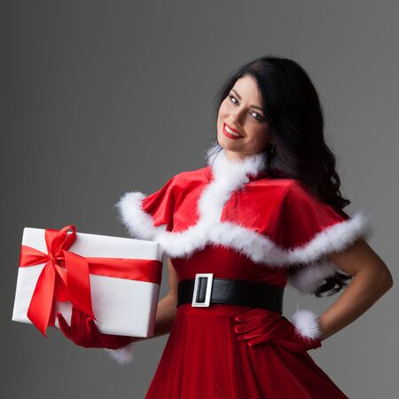 Smiling cute girl in red christmas outfit holding gift box
