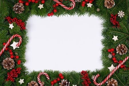 Christmas Border frame of tree branches on white background with copy space isolated, red and white decor, berries, stars, cones Stockfoto