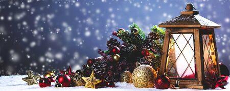 Burning candles , lantern and christmas decoration on snowfall background Stockfoto
