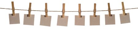Set of eight blank paper notes held on a string with clothespins isolated on white background