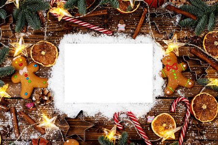 Christmas food frame. Gingerbread cookies, spices and decorations on wooden background with copy space on snow Stockfoto