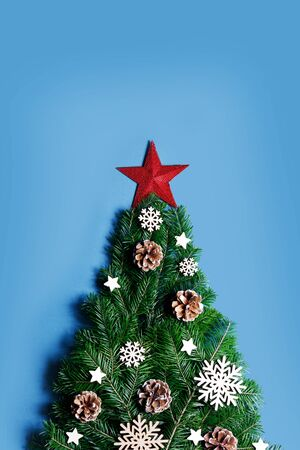 Christmas tree made of natural spruce branches deecor with red star on blue background, flat lay card with copy space Stockfoto