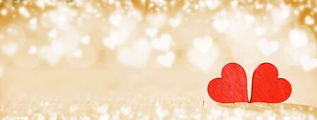 Two handmade wooden red hearts on beautiful bokeh background. Vintage style. Love Valentines Day concept. Stock Photo