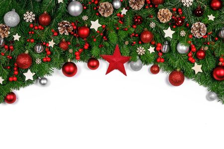 Christmas Border frame of tree branches on white background with copy space isolated, red and golden decor, berries, stars, cones Stockfoto