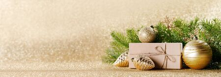 Christmas toys, decorations, present gift box wrapped in kraft paper on golden glitter background, copy space Stockfoto