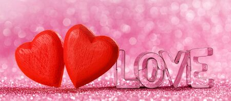 Two red handmade wooden hearts and word love on pink bright glitter lights bokeh background