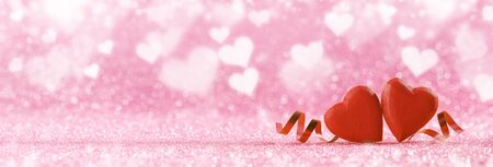 Two red handmade wooden hearts and ribbons on pink bright glitter lights bokeh background