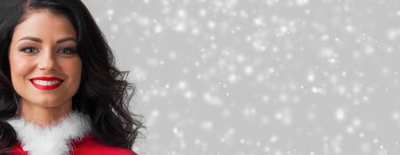 Beautiful happy woman in Santa Claus clothes on glowing lights bokeh background Stockfoto