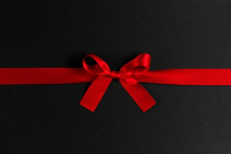 Shiny red satin ribbon and bow on black background. Holiday gift concept Stockfoto