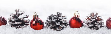 Red Christmas balls and pine cones in a row in snow isolated on white background