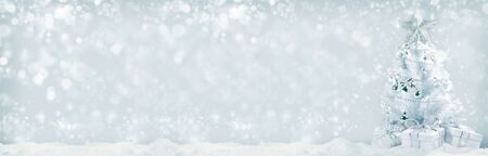 White christmas tree with silver decorations and gifts on snow on bokeh background Stockfoto
