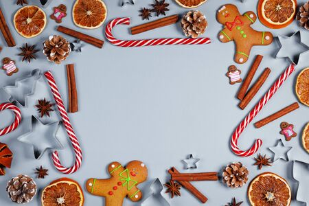Christmas food frame. Gingerbread cookies, spices and decorations on blue background with copy space