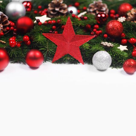 Christmas Border frame of tree branches on white background with copy space isolated, red and silver decor, berries, stars, cones