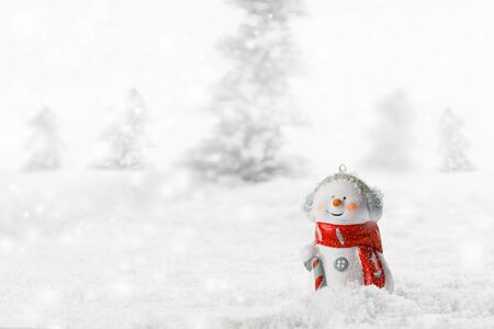 Christmas Snowman toy on winter forest background in the snow