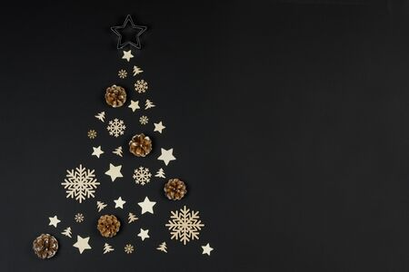 Christmas Tree made of wooden decor and pine cones on black paper background. Christmas Holiday Concept. Flat Lay Stockfoto