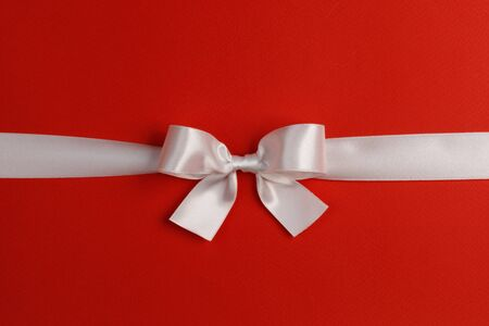White gift bow on red background copy space for text
