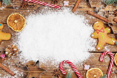 Christmas food frame. Gingerbread cookies, spices and decorations on wooden background with copy space on snow Stock Photo