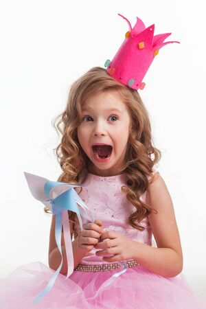Beautiful little candy princess girl in crown holding pinwheel and screaming in joy