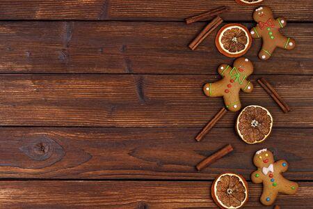 Weihnachtsflacher Laienhintergrund mit traditionellen Lebkuchenplätzchen getrockneter Orangen-Zimt auf Holz
