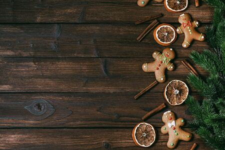 Christmas flat lay background with traditional gingerbread cookies dried orange cinnamon and fir tree on wood