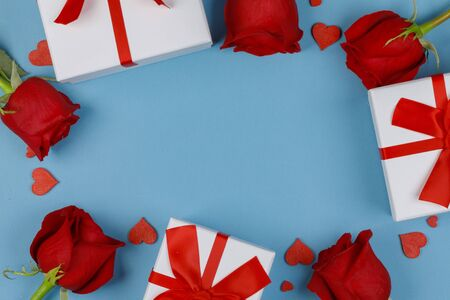 Red roses gifts and red hearts composition on blue background top view with copy space. Valentine's day, birthday, wedding, Mother's day concept. Copy space Standard-Bild - 133947739