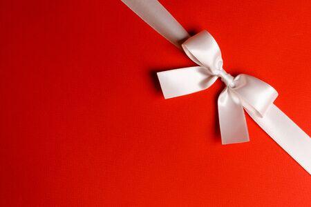 Elegant satin white ribbon bow on red background