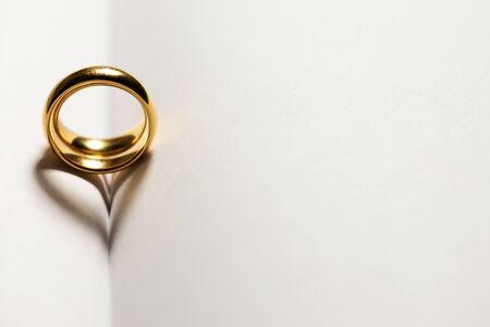 Due fedi nuziali dorate sullo sfondo delle pagine del libro bianco con lo spazio della copia per il testo Archivio Fotografico