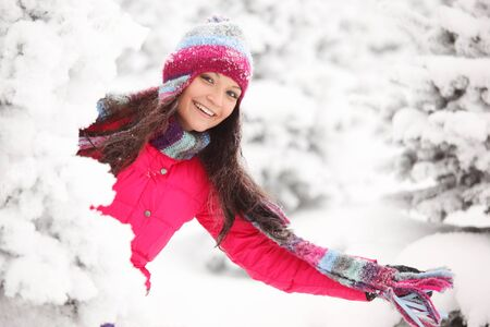 Happy smiling playful woman having fun in winter snow covered forest Stock Photo